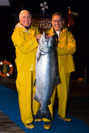 Two Rivers Inlet Sportsman's Club guests in yellow rain-gear are back at the dock in the evening showing off their 62 lbs Chinook Salmon