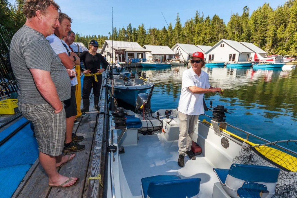 A Rivers Inlet Sportsman's Club fishing guide stands in a boat at the dock while giving instructions to a group of guests who watch