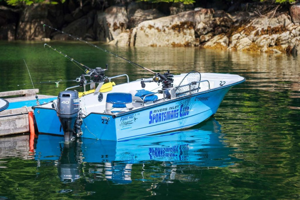 An empty blue Sportsman's Club fishing boat is parked at the dock ready for the next guest to jump in and go out to slay some salmon.