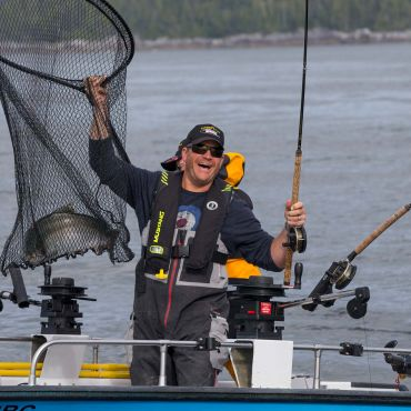 A Rivers Inlet Sportsman's Club guest is in his boat shouting emotions of accomplishment as holds up his net showing off the salmon he just caught