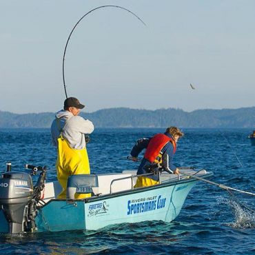 A father and young son are in action netting a fish from a Rivers Inlet Sportsman's Club fishing boat in the ocean.