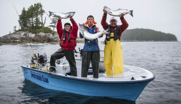 3 men in a boat in ocean waters of Rivers Inlet BC with the islands behind them. They are each holding a large king salmon above their head and hollering with glee!
