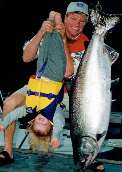 Man holding 2 year old child by ankles upside down comparing her to the size to a 60 lbs King Chinook salmon hanging upside down beside her