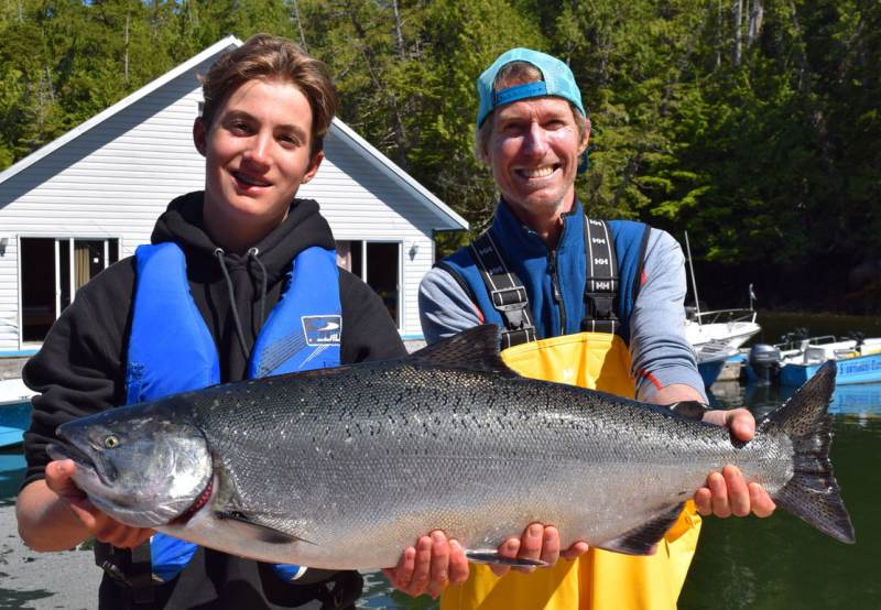 Father and son smiling while proudly holding their King salmon caught on their BC salmon fishing trip